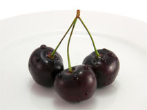 Black cherry on a white plate close-up Stock Photos