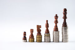 Black chess figures standing on coins meaning power and career growth Stock Photography