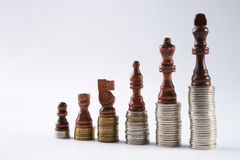 Black chess figures standing on coins meaning power and career growth Royalty Free Stock Photos