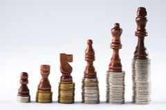 Black chess figures standing on coins meaning power and career growth. Growing coins stacks on white background. Black chess figures standing on coins meaning stock photography