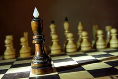 Black chess king in front of enemy team. Unequal fight Royalty Free Stock Photo