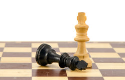 Black chess king lie near winner white legs Royalty Free Stock Photos
