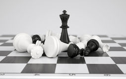 Black chess king in the midst of battle. Gray background Royalty Free Stock Photography