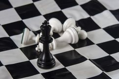 Black chess king standing on chessboard, white king fallen with stock photos