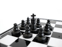 Black chess king stands on a chess board with figures royalty free stock photos