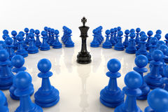 Black chess king surrounded by blue pawns. High quality 3D render of black chess king encircled by over fifty blue pawns. Superb reflections and medium depth of Stock Photography