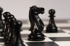 Black Chess Knight in Opening Game. An ebony black chess knight in the traditional Staunton design moves out over the pawn line in the opening part of a game Stock Photo