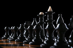 Black chess pieces. On the board isolated on a black background Royalty Free Stock Images