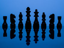 Black chess pieces. On blue background royalty free stock photography