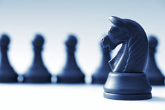 Black chess pieces and horse on a light blue background Royalty Free Stock Photo
