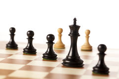 Black chess pieces with white pawns in the background Stock Photos