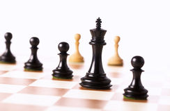 Black chess pieces with white pawns in the background Stock Image