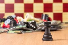Black chess rook on the blurred background of other objects for popular board games. Black Chess Rook on a blurry background of a chessboard and other objects Royalty Free Stock Image