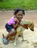 Black child and dog. Happy African child caresses her dog Stock Photo