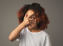 Afro kid girl peeking though fingers on gray background. Black child girl peeking in shock through fingers royalty free stock photo