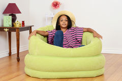 Black child relaxing in green chair Royalty Free Stock Image