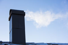 Black chimney of the house, which becomes smoke. Royalty Free Stock Image