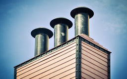 Black chimneys against the blue sky Stock Photo