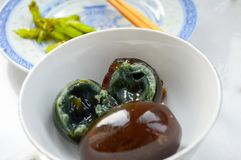 Black Chinese Century Eggs in White Bowl. Chinese Century Eggs in White Bowl. One Egg Cut in Half Shows Black Soft Yolk Inside Stock Photos