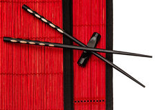 Black chinese chopsticks on red bamboo mat. asian style Royalty Free Stock Photos