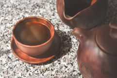 Black Chinese Puer tea brewed in a clay cup. Composition of ceramic ware for tea ceremony.  Royalty Free Stock Image