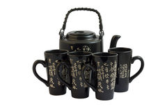 The black chinese teapot and cups. The black chinese teapot and four cups on white Royalty Free Stock Photos
