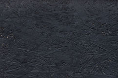 Black chipboard also called particleboard. Background texture.