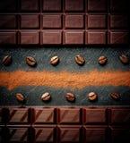 Black chocolate bar, coffee beans, cocoa powder on black. Slate plate royalty free stock photo