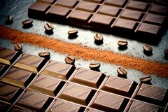 Black chocolate bar, coffee beans, cocoa powder. Top view royalty free stock photography