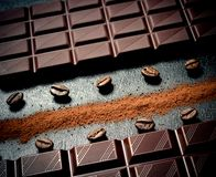 Black chocolate bar, coffee beans, cocoa powder. Top view royalty free stock photos