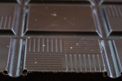 Black chocolate cubes broken and stacked on each other. Sweet de Stock Photo