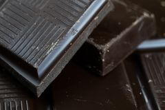 Black chocolate cubes broken and stacked on each other. Sweet de Royalty Free Stock Images