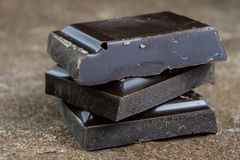 Black chocolate cubes broken and stacked on each other. Sweet de Stock Images