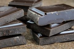 Black chocolate cubes broken and stacked on each other. Sweet de Royalty Free Stock Photography