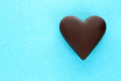 Black chocolate heart on blue background Stock Photo
