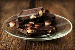 Black chocolate with nuts in a glass saucer Stock Photos