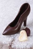 Black chocolate shoe with candy hearts Stock Photography
