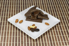 Black chocolate on a white plate. Dark chocolate and nuts with raisin on a white plate Royalty Free Stock Photo