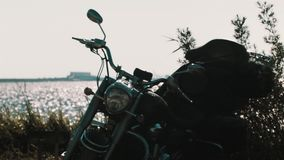 Black chopper motorcycle parked in bushes on sea shore. Black chopper motorcycle parked in bushes on sea shiny water surface shore, sunny summer day stock video