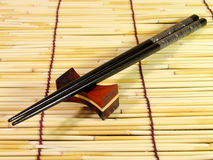 Black chopsticks. Over the bamboo straws floor Royalty Free Stock Photo