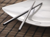 Black chopsticks on a plate. Elegant chopsticks rest on white plate stock photo