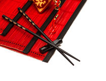 Black chopsticks on red bamboo mat. Chinese new years lucky char Stock Photo