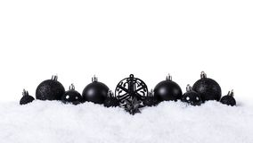 Black christmas balls with snow isolated on white background.  royalty free stock photography
