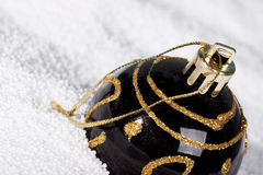 Black Christmas bauble on to snow. Royalty Free Stock Photo