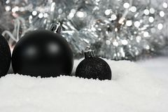 Black Christmas baubles nestled in snow. With silver bokeh lights background Royalty Free Stock Photo