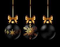 Black Christmas decoration ball with golden ribbon bow on black background. Black Christmas decoration balls collection on black background. Confetti backdrop Stock Photography