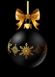 Black Christmas decoration ball with golden ribbon bow on black background. Royalty Free Stock Images