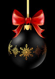 Black Christmas decoration ball with golden ribbon bow on black background. Stock Images