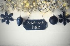 Black Christmas Plate, Fairy Light, Text Save The Date. Black Chirstmas Plate With English Text Save The Date. Fir Branch With Fairy Lights On Wooden Background Royalty Free Stock Image