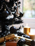 Black christmas tree gold candle. Modern Christmas tree in black with black and silver christmas balls and gold candel plus crackers Royalty Free Stock Photos